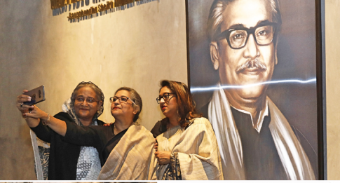 PM takes selfies with her sister, daughter in front of a portrait of Bangabandhu