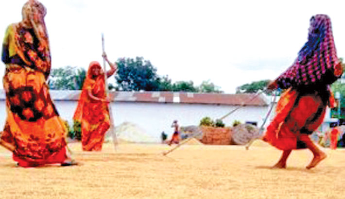 Women are seen busy drying paddy