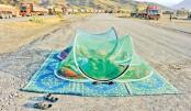 Afghan civilians sleep along a road near the Torkham border