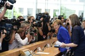 Angela Merkel stands by refugee policy after attacks