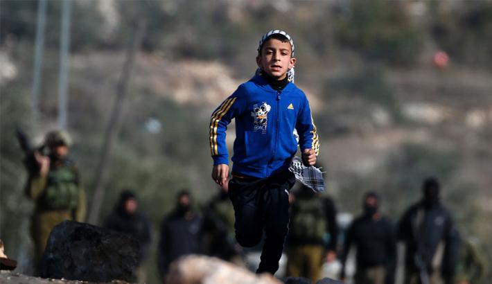 A Palestinian boy runs back