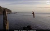 1,000 feet above a choppy sea, sharp rocks, this man walks on rope (Video)