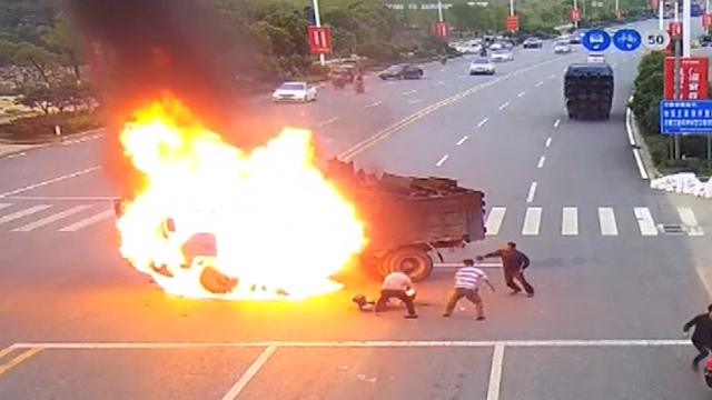 Biker miraculously survives after crashing into truck which burst into flames (Video)
