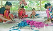 Craftswomen are seen busy making hand fans