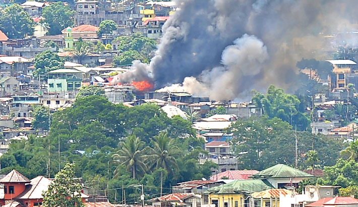 Smoke billows from burning buildings in Marawi
