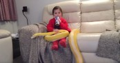 Video shows fearless girl casually pat her pet python while sipping milk