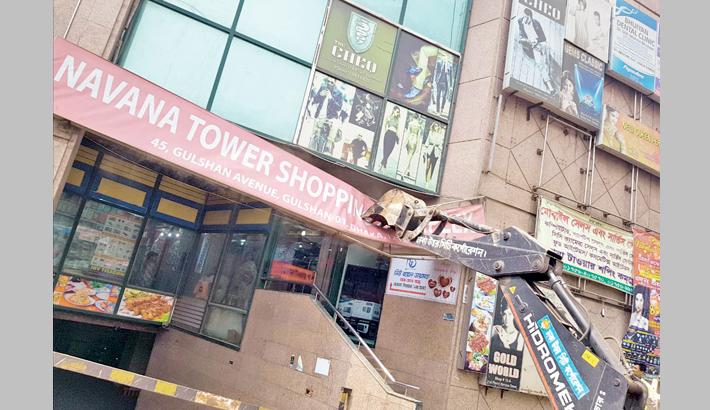 A DNCC bulldozer removes a huge signboard