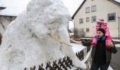 A man and a child look at an elephant made of snow
