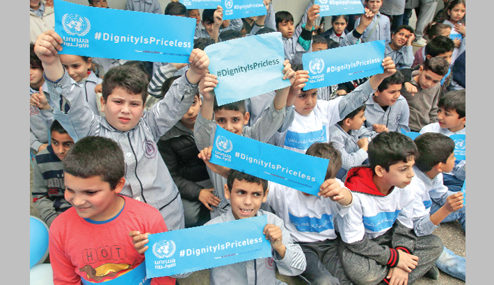 Palestinian refugees hold placards