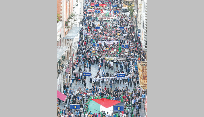 Demonstrators march with a giant Palestinian flag