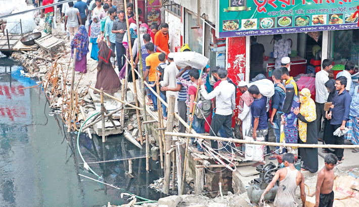 Bamboo and wooden bridges to cross a canal, risking accident