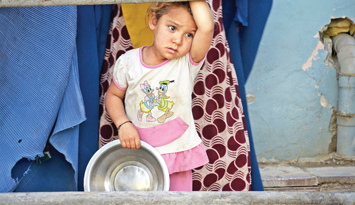 Afghan girl looks on as she waits to receive food donated by a private charity