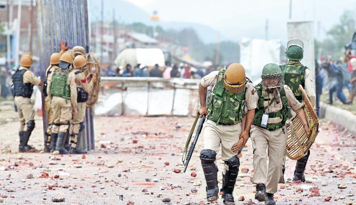 Injured policeman walks back during clashes