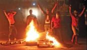 Iraqi protestors burn pieces of wood