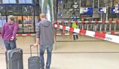 Passengers are pictured in front of police cordon tape