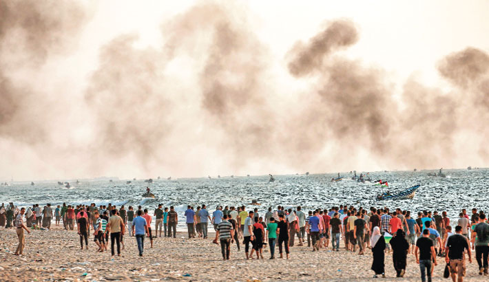 Palestinians protest on a beach along the Gaza sea barrier