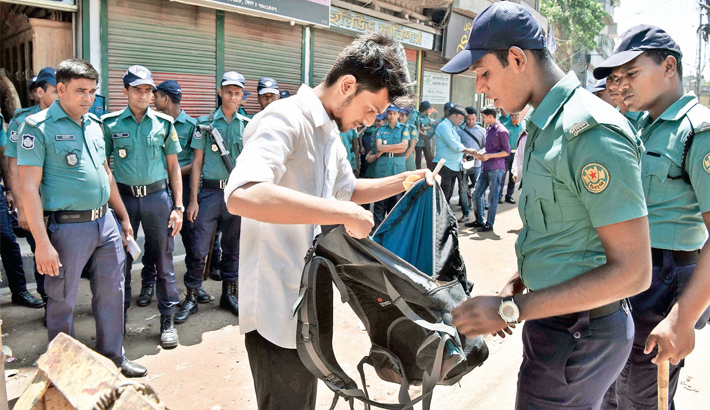 Policeman searches the school bag of astudent