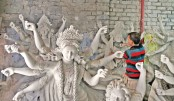 Artisan works on an idol for Durga Puja