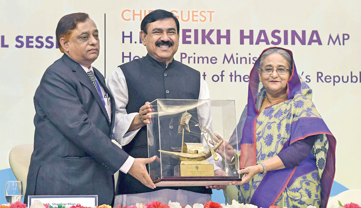 Shipping Minister Shajahan Khan hands over a crest to Prime Minister Sheikh Hasina