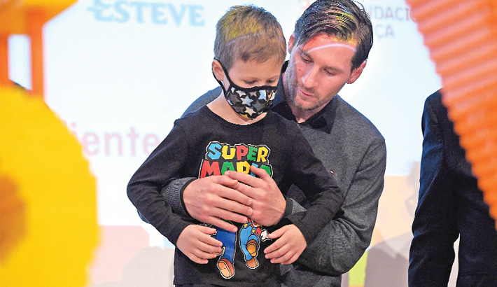 Lionel Messi poses with a child