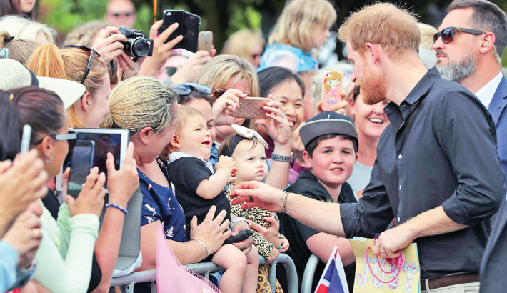Britain's Prince Harry greets a toddler during a public walkabout