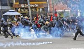 Protesters run during clashes with the police