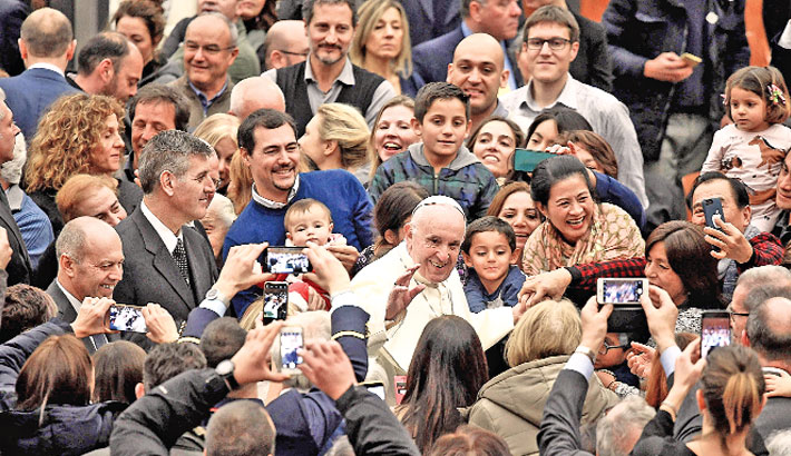 Pope Francis (C) arrives for an audience with the Vatican employees