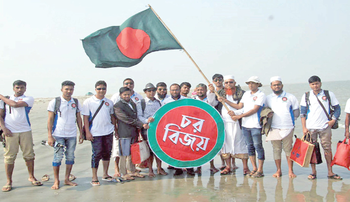 Tourists hold up a Bangladeshi flag and placard in Chor Bijoy