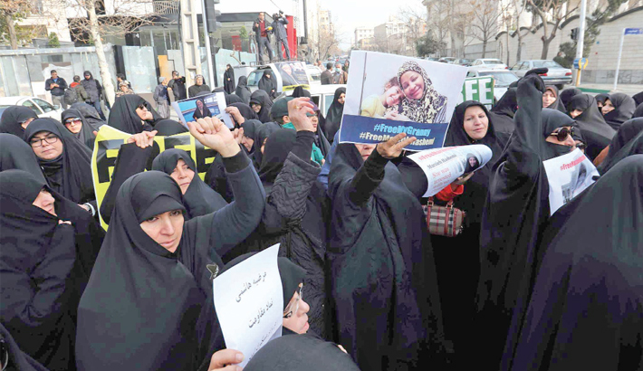 Iranians hold banners bearing messages