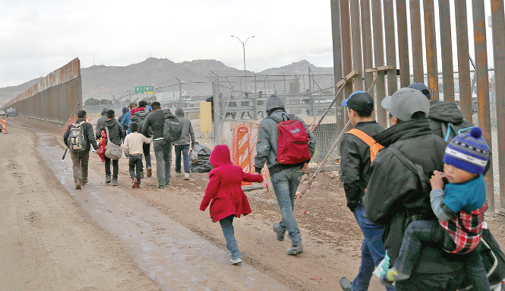 Central American immigrants walk between a gap in the border fence