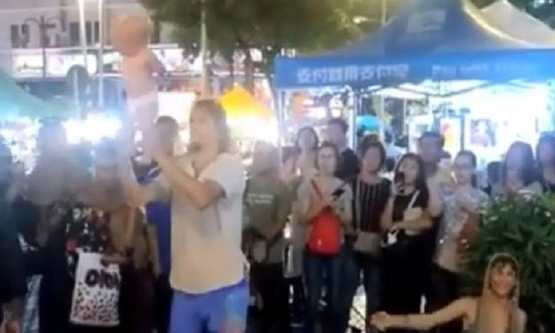 Russians detained over baby swinging street act in Malaysia