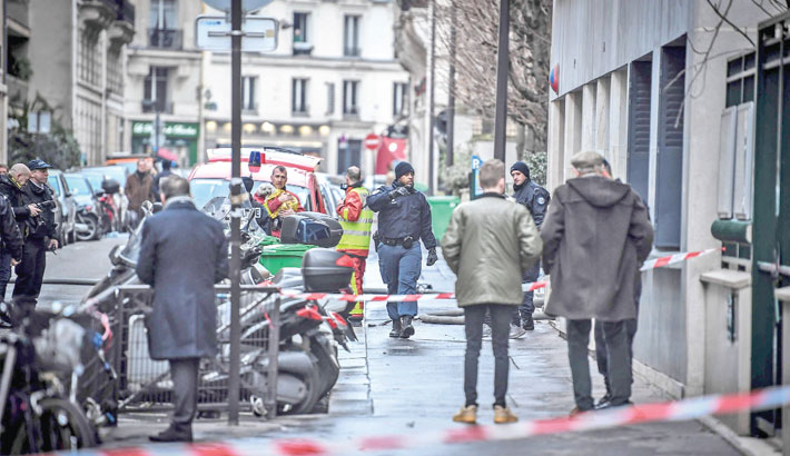 Firefighters are seen near a building that caught fire in the 16th arrondissement