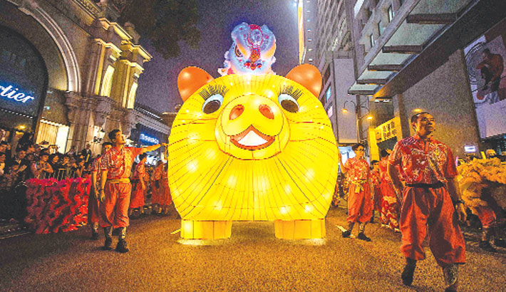 Performers walk with a lit model of a pig during the annual Lunar New Year parade