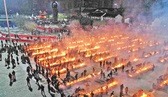 Chinese worshippers offer prayers and burn incense on the fifth day