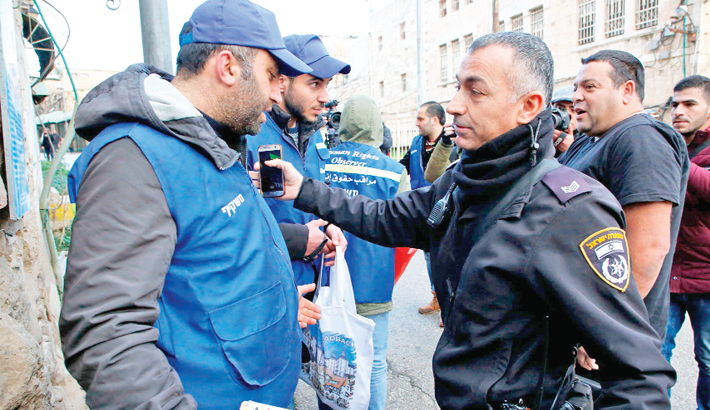 Israeli security forces speaks to members of the Palestinian Youth