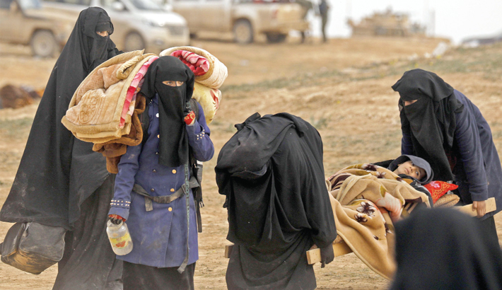 Civilians fleeing the Islamic State's group embattled holdout of Baghouz walk