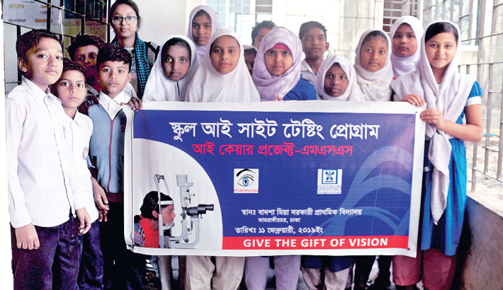 Students of Badsha Mia Government Primary School hold a banner prior