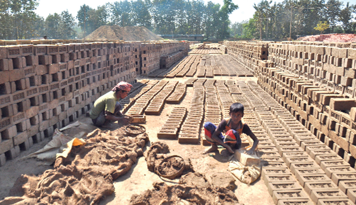 A child labourer makes raw bricks and dries