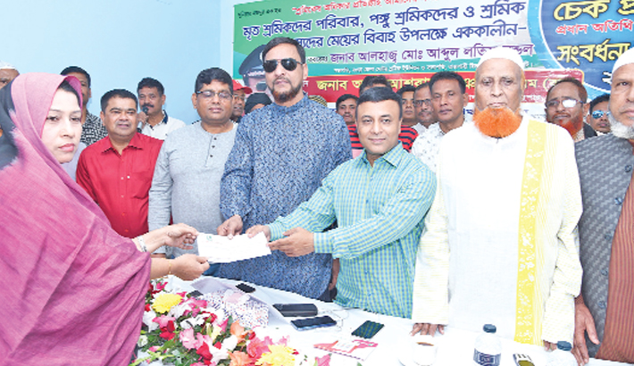 Hand over a cheque of financial assistance to a woman