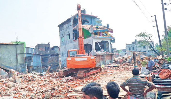 A bulldozer of the Bangladesh Water Development Board authorities demolishes a four-storey building constructed illegally