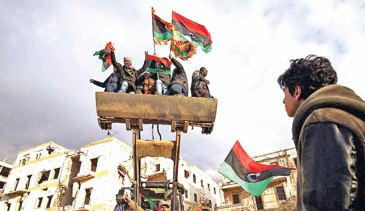 Libyan men on a bulldozer wave the national flag