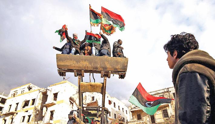 Libyan men on a bulldozer wave the national flag