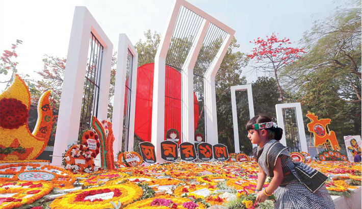 A child places flowers at the altar of the Central Shaheed Minar in the capital