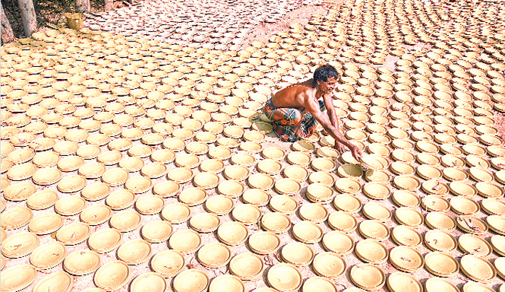 Potter is drying earthen pots in sun