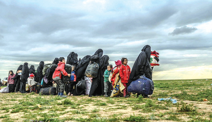 Women and children wait to be searched by members of the Kurdish-led Syrian Democratic Forces