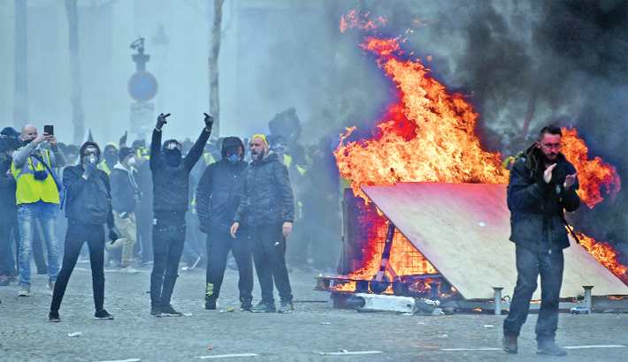 Protesters gather during clashes with riot police forces on the Champs-Elysees in Paris