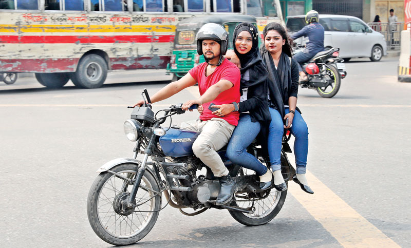 A man rides a motorbike with two pillion riders