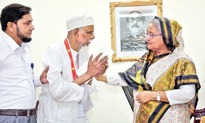 Prime Minister Sheikh Hasina consoles an ailing man after providing