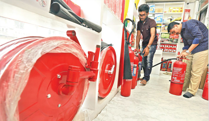 Two persons examine fire safety equipment before purchase at a shop in the capital's Nawabpur area
