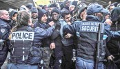 French security agents and police officers hold back migrants